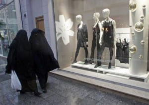Women wearing niqabs walk past clothes shops on the street in Marseille December 24, 2009. France's ruling UMP party plans to present a bill to parliament in January that aims to ban full Islamic veils in all public places and not only in certain buildings and the bill would be accompanied by a resolution related to respect for women.  Both propositions would be handed to parliament during the first two weeks of January, before the conclusions of a French parliamentary inquiry into the all-covering niqab and burqa are unveiled.  REUTERS/Jean-Paul Pelissier   (FRANCE - Tags: RELIGION POLITICS) - RTR28BU2