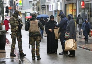 """Belgian soldiers and a police officer control the documents of a woman in a shopping street in central Brussels, November 21, 2015, after security was tightened in Belgium following the fatal attacks in Paris. Belgium raised the alert status for its capital Brussels to the highest level on Saturday, shutting the metro and warning the public to avoid crowds because of a """"serious and imminent"""" threat of an attack. REUTERS/Youssef Boudlal - RTX1V5AF"""